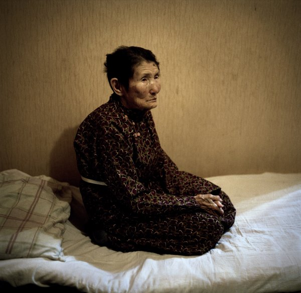 Adiya, 91. She lives with six members of her family in a two-room dwelling. She sleeps on the floor, next to her two great-grandchildren.   Ulan Bator city centre, December 2011.