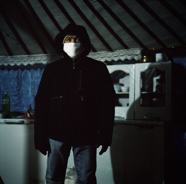 Monkhjargal covers his mouth before going out in order to avoid inhaling the coal particles that permeate the city. Coal is used to fuel the stoves in most yurts.   Yurt neighbourhood of Sükhbaatar, Ulan Bator, December 2011.